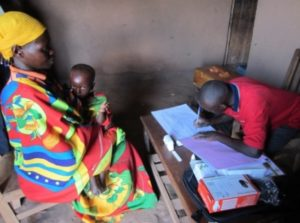 A community health worker consulting a sick child in his home. Photo credit: Jane Briggs SIAPS