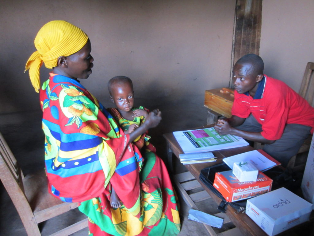 A community health worker attends ti a sick child brought by the child's caregiver in a rural village in Burundi. Photo: Jane Briggs